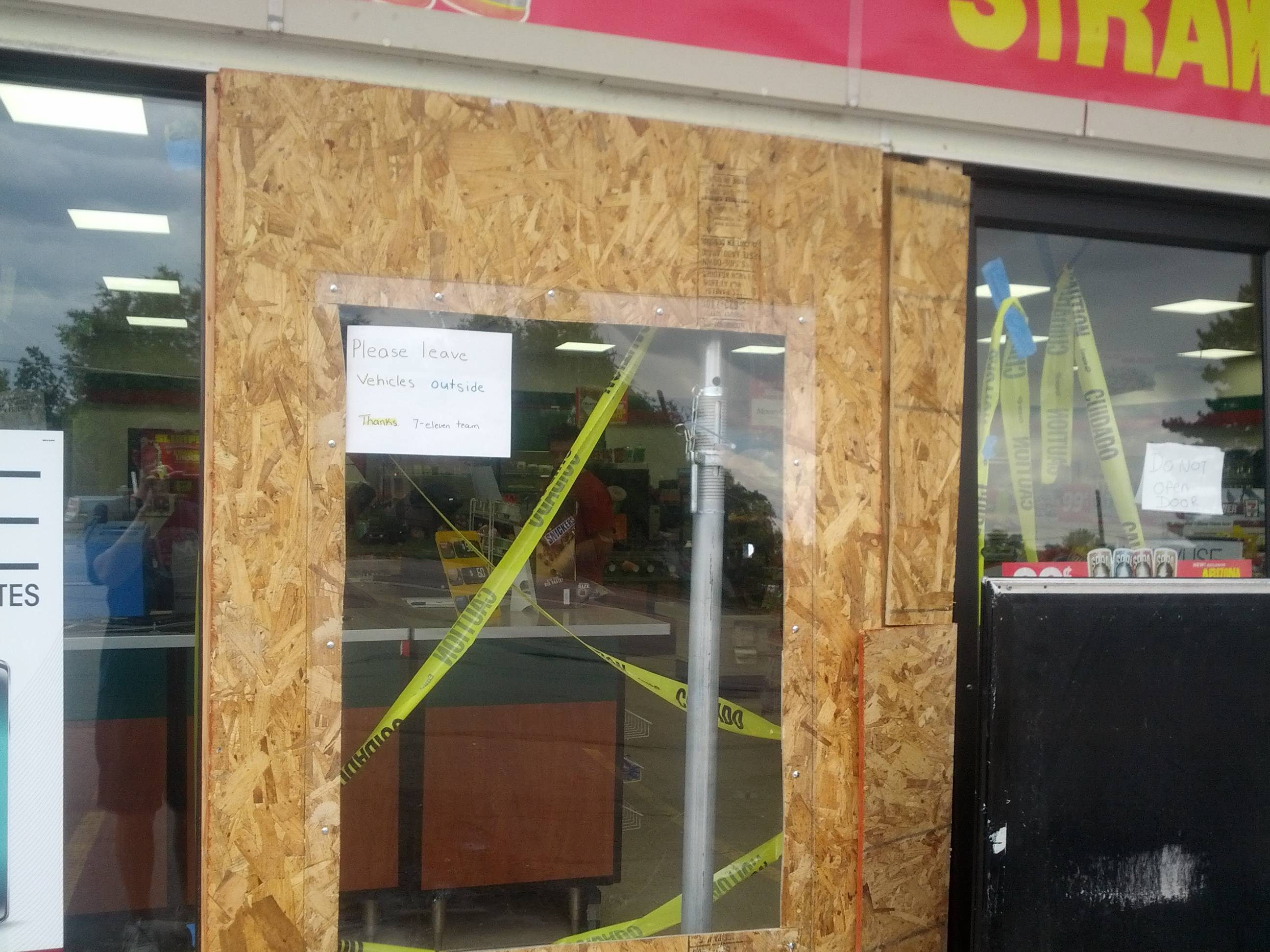 The door of 7/11 has been replaced by plaster and is being repaired because a car drove through it. A paper says please leave cars outside.