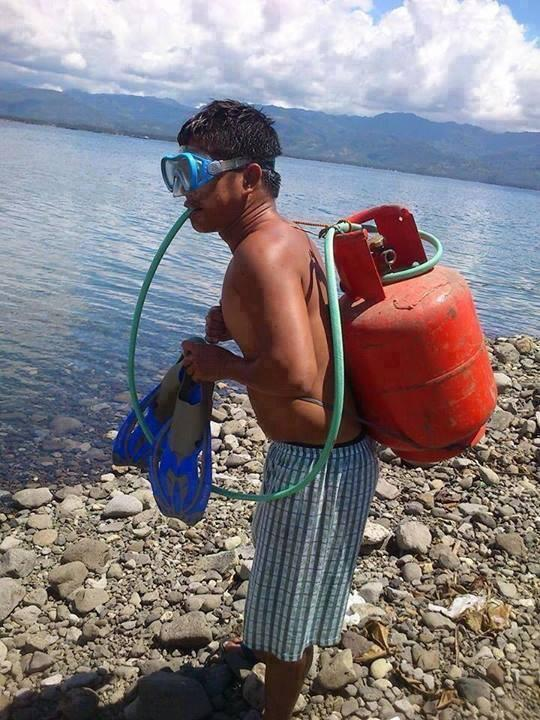A man is geared with a propane tank and a hose is connected from his mouth to the tank.